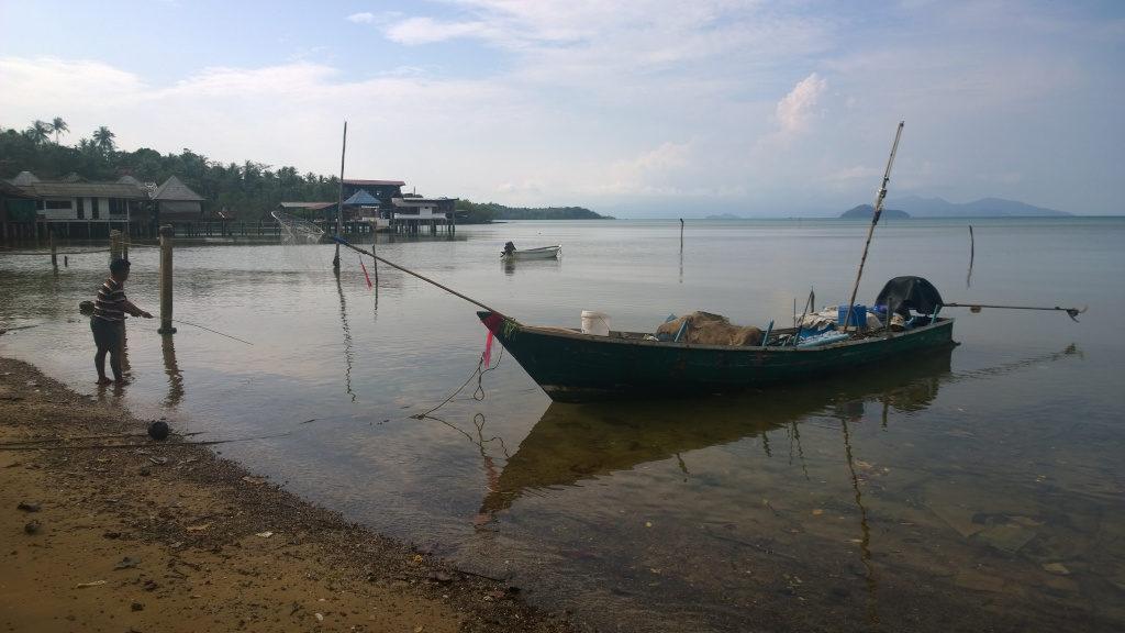 Un pescatore in riva accanto ad una long-tail boat in riva