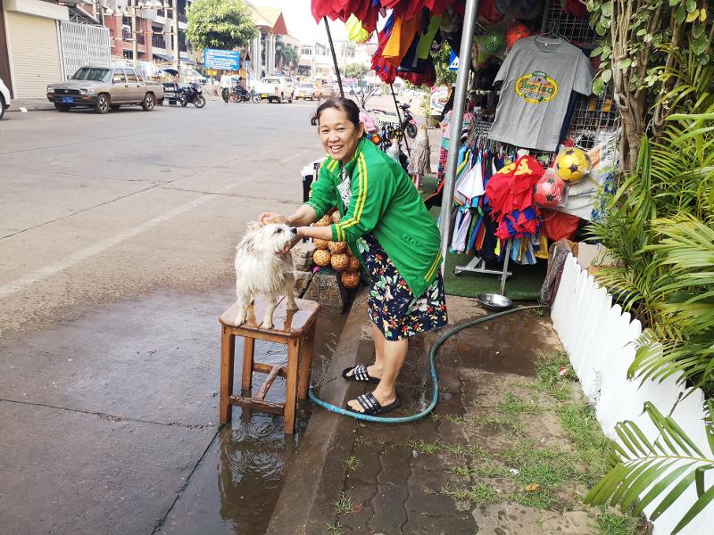Una donna Laotiana lava il suo cane