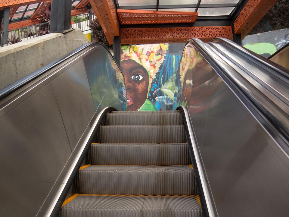 Scala mobile con murales della stazione di Medellin