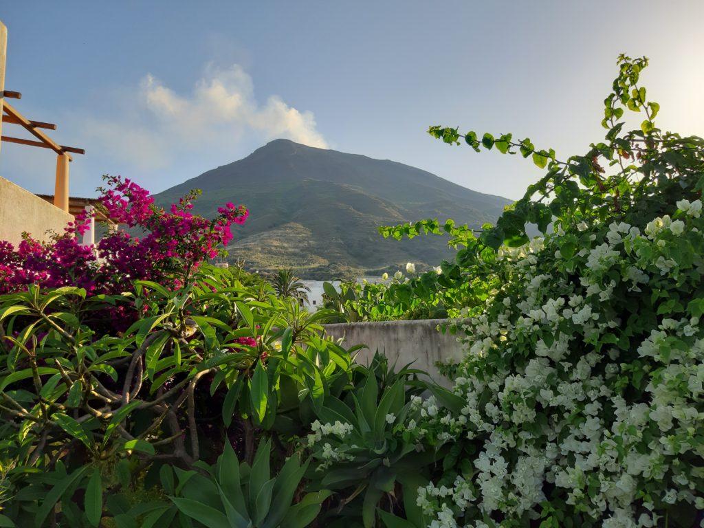 Vista sul vulcano Stromboli illuminata da bouganville bianca e viola